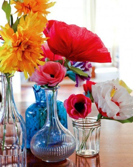 Разноцветные цветы в стеклянных емкостях