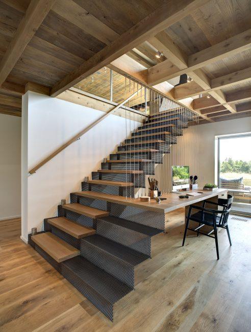 Интересное и функциональное решение — одна из ступеней лестницы плавно перетекает в письменный стол