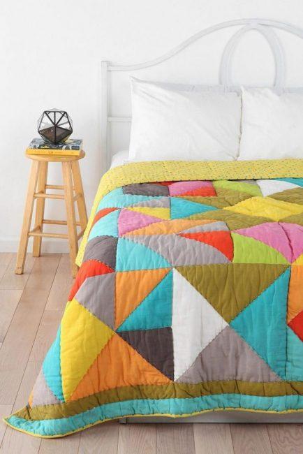 Яркое стеганое одеяло поверх кровати для уюта