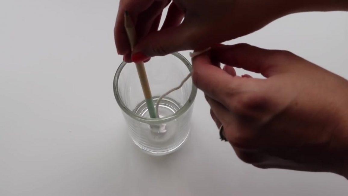 Окуните конец фитиля в расплавленный воск, а затем быстро прикрепите его