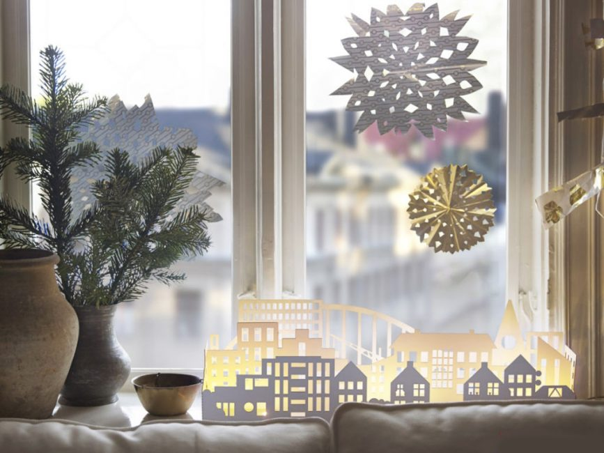 Силуэт новогоднего города, вырезанного из бумаги, уютно будет смотреться, если разместить внутри свечи