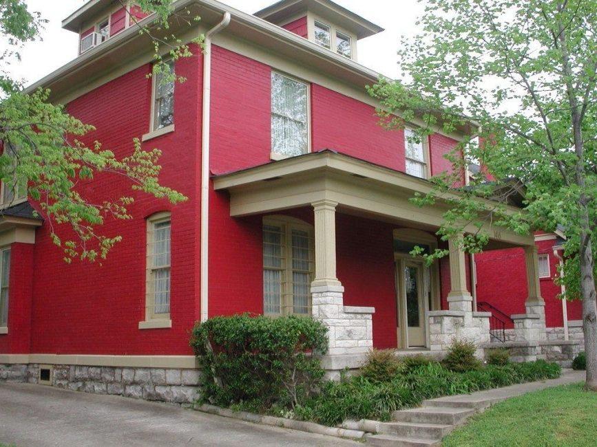 Стены, выкрашенные в насыщенно-красный цвет, и бежевые колонны выглядят изысканно