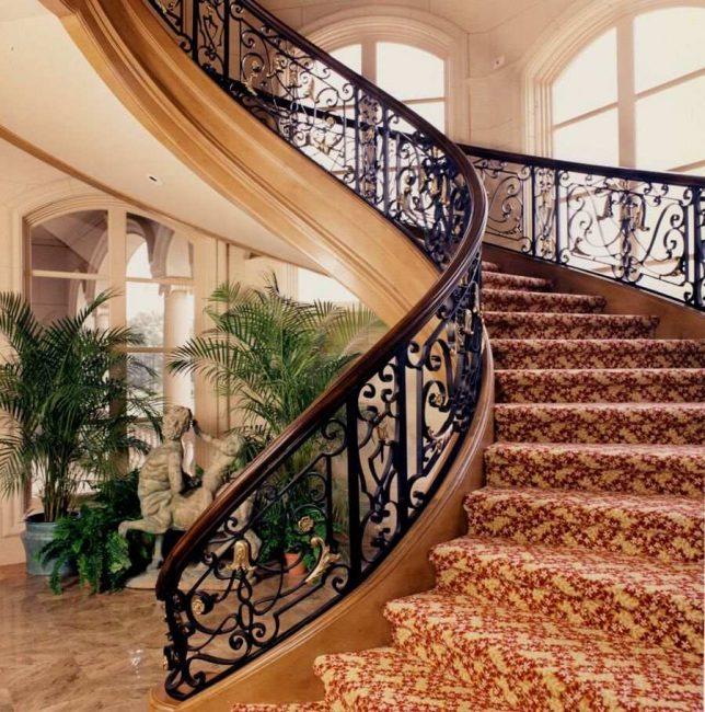 Сочетание ковки, дерева и коврового покрытия в дизайне лестницы