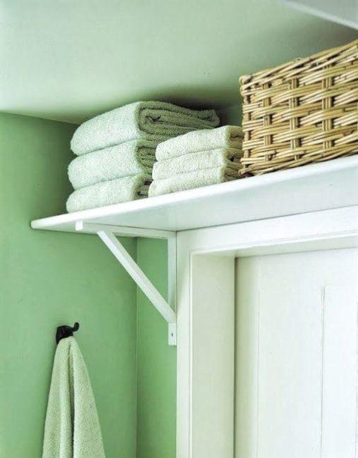 Используйте пространство над дверью, чтобы хранить там запасные полотенца или корзинки с бытовой химией.
