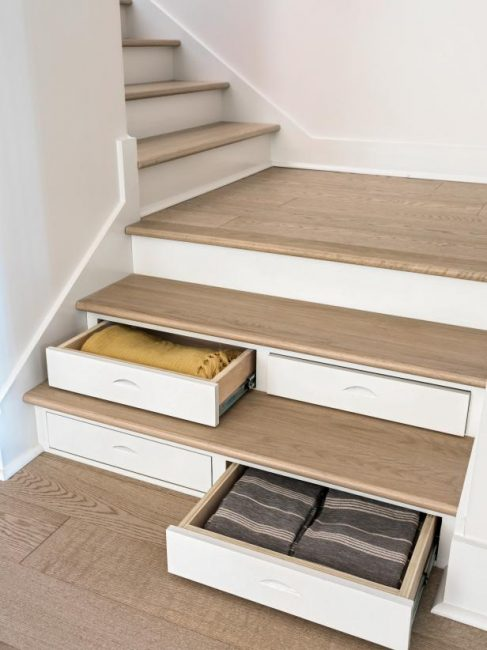 Если в вашем доме есть лестница, используйте пространство под ступеньками. Из него могут получиться полноценные ящики для белья или других вещей