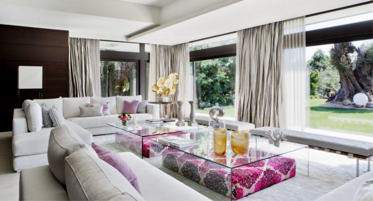 Шикарная гостиная выполнена в спокойных бежевых тонах. Ее дополняют огромные диваны и панорамные окна