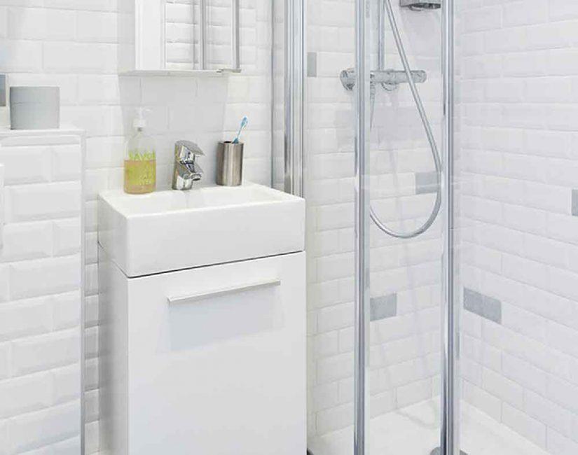 Ванная выложена плиткой с фацетом. Здесь есть раковина, душ и унитаз