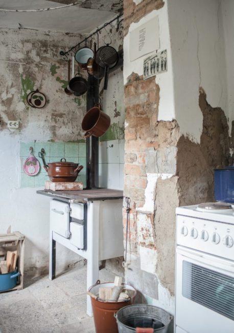 На кухне — минимум посуды и техники, а также дровяная печь