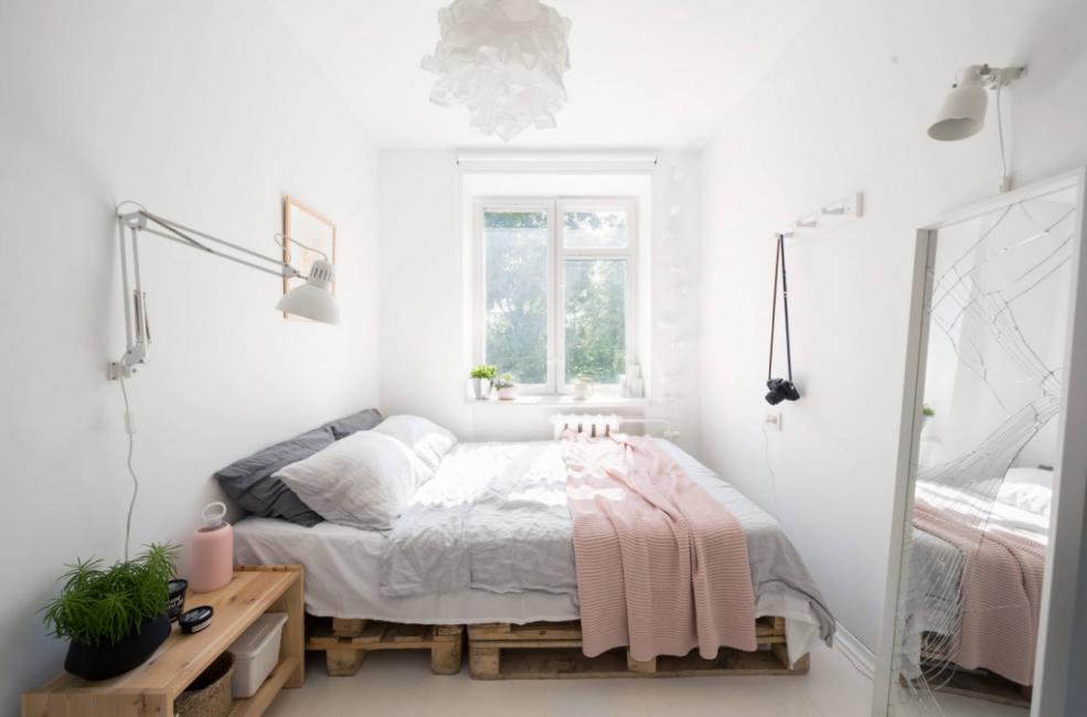 В спальне — просторная кровать, которая стоит на деревянных поддонах