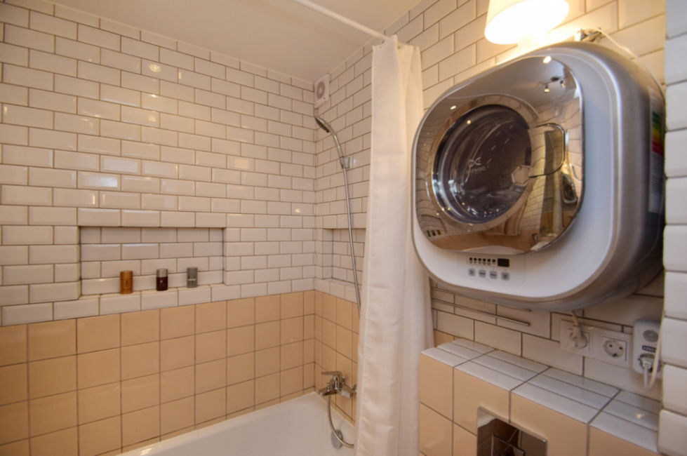 Ванная комната выполнена в теплых тонах из бежевого кафеля