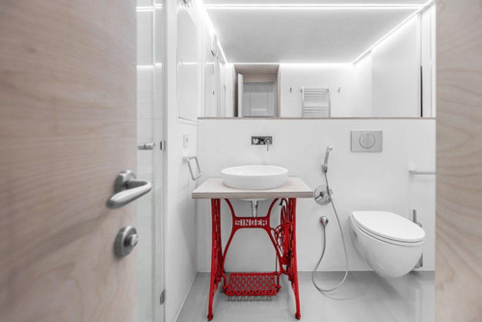 Сама ванная комната выполнена в светлом оттенке с яркими красными акцентами