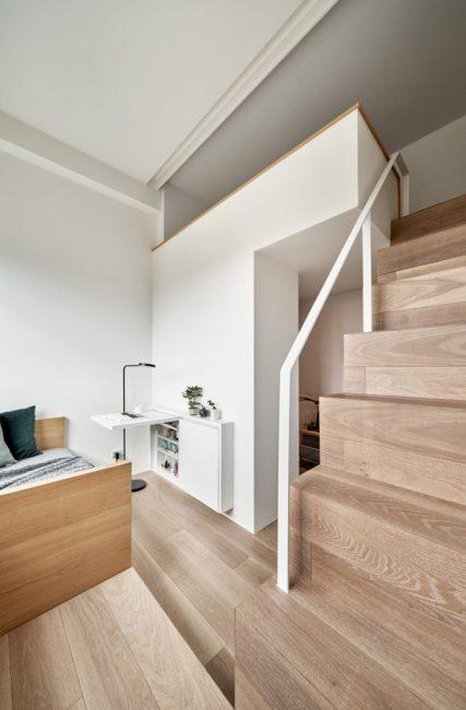 Бетонная балка, проходящая через квартиру, стала разделителем помещения, а пространство под ней превратили в настенные шкафы