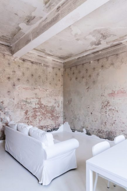 Вместо привычного телевизора, напротив дивана — глухая стеная с опавшей штукатуркой