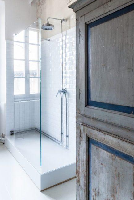 Невероятный контраст между современной стеклянной душевой кабиной и старинным шкафчиком