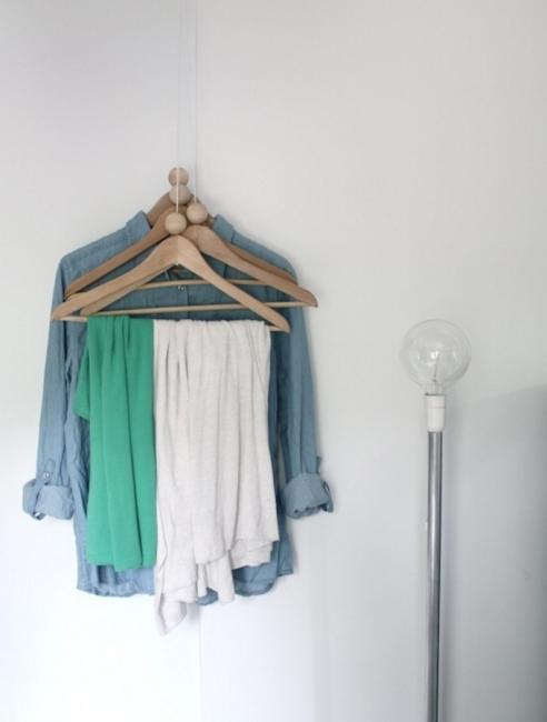 Вещи не обязательно хранить в шкафу. Подвесьте плечики прямо на стену