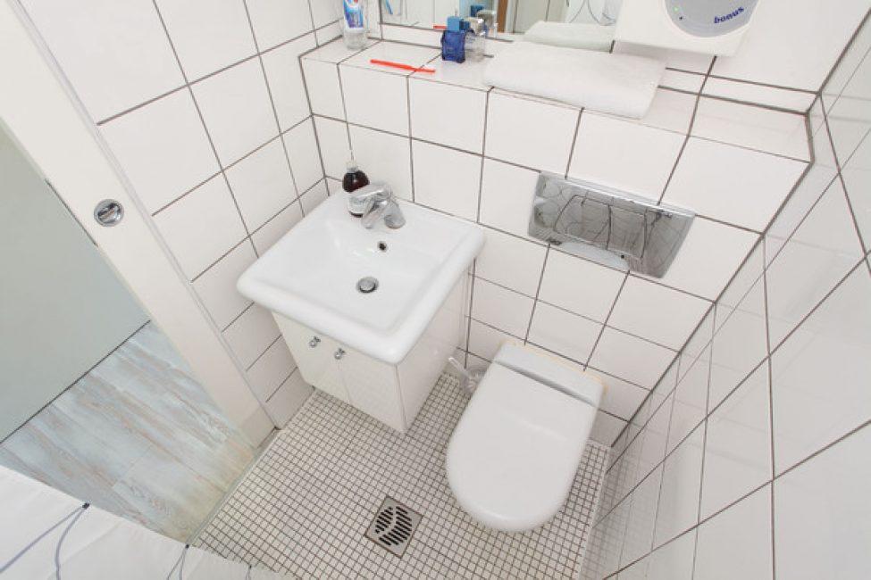 Ванная комната выполнена в белом цвете, в нее поместилась самая необходимая сантехника
