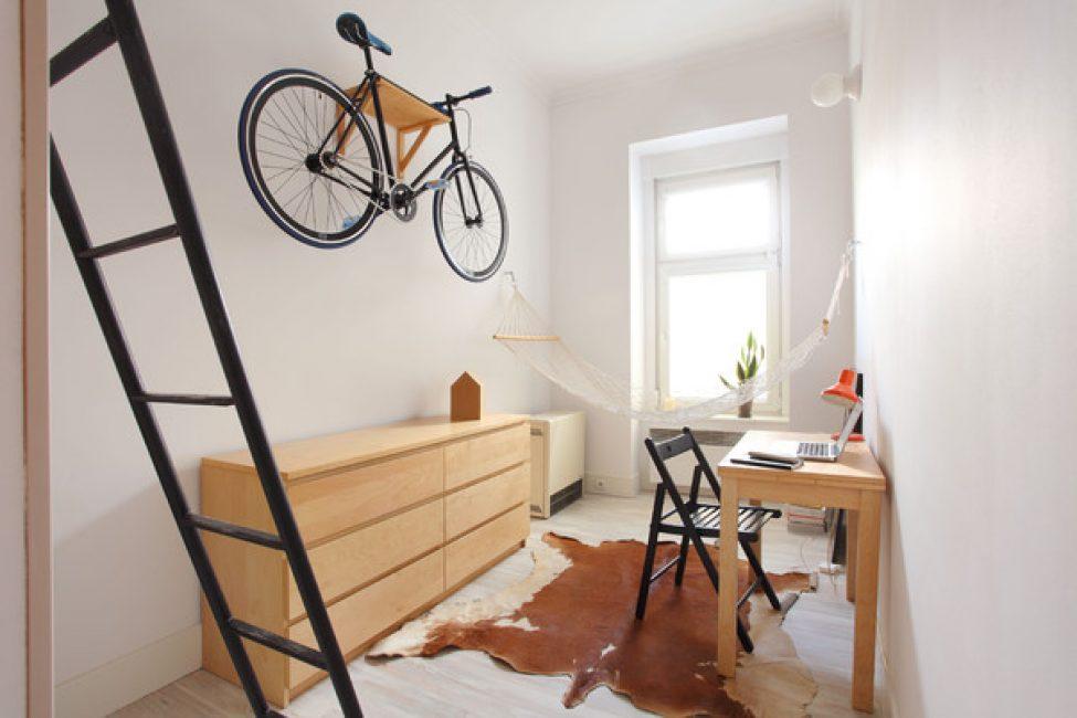 В гостиной поместился рабочий стол, комод, гамак и велосипед, прикрепленный на стену