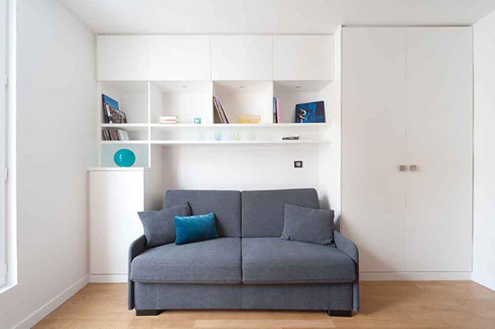 Удобный шкаф-стеллаж за диваном вмещает в себя все необходимые вещи