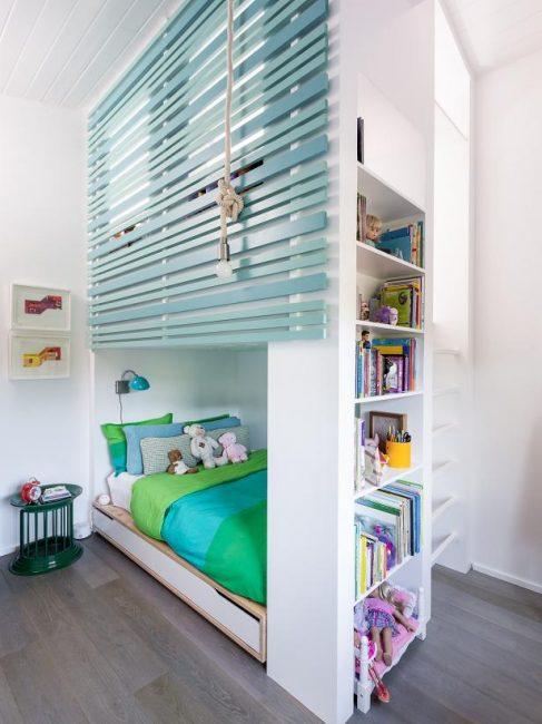 В этой детской комнате установлена двухъярусная кровать со встроенным книжным шкафом с дополнительным местом для хранения вещей
