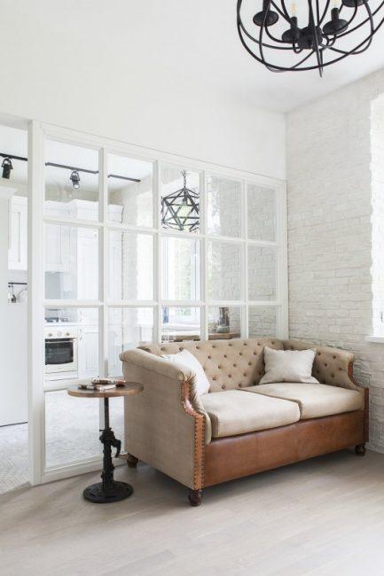Особого шарма интерьеру придает стеклянная перегородка, которая отделяет зону гостиной от кухни
