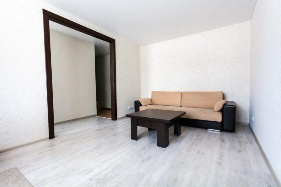 Зал оформили в стиле минимализм, со светлым ламинатом и белыми стенами