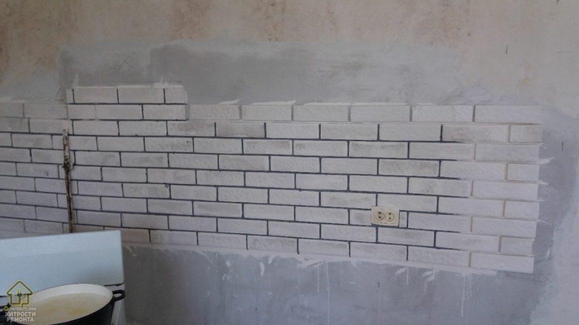 Стену, у которой планировали поставить мебель и технику, также выложили белым кирпичом. Но гладким, а не фактурным