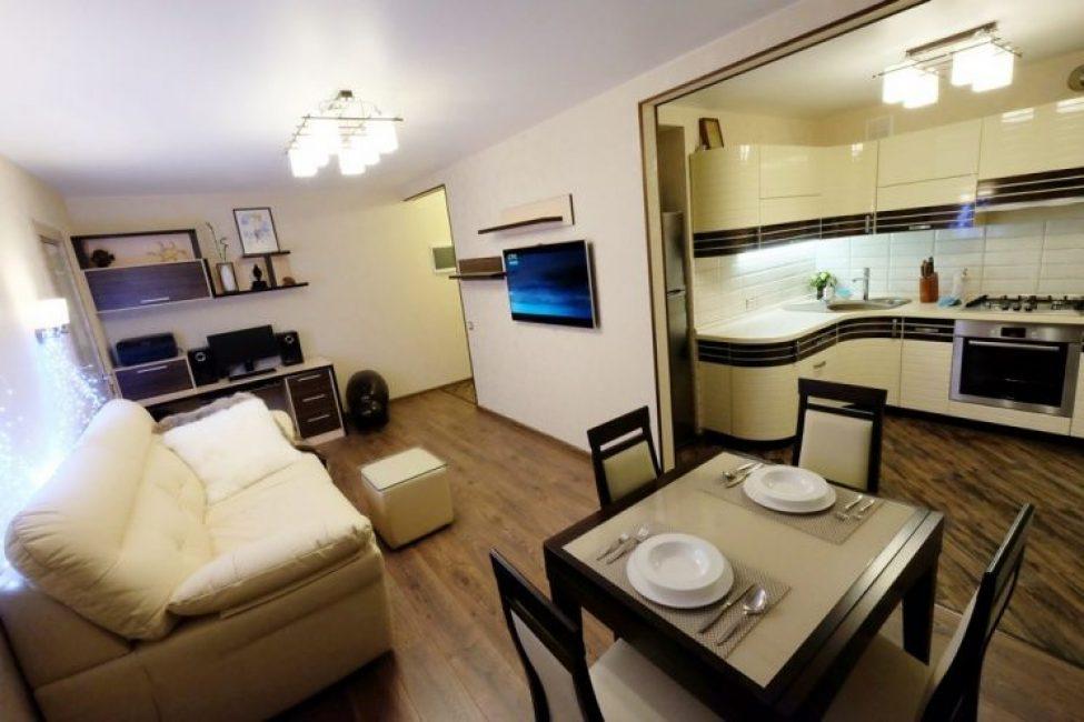 В зале расположился белый кожаный диван в классическом сочетании плазмы напротив него на стене