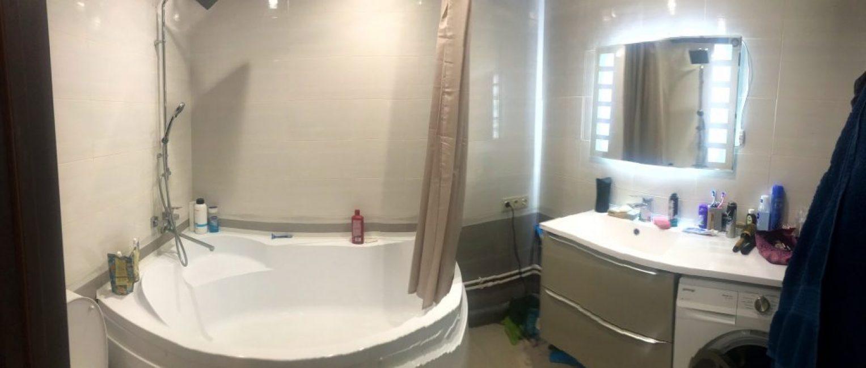 Совмещенный санузел с большой угловой ванной выполнен в светлом оттенке