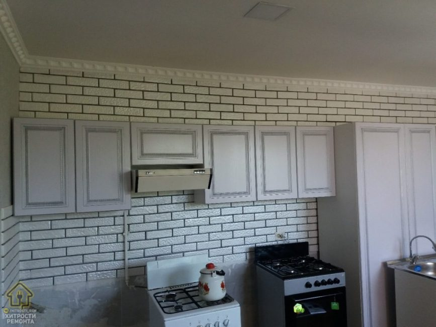 На фоне всего белого явно выделяется новая черная кухонная плита