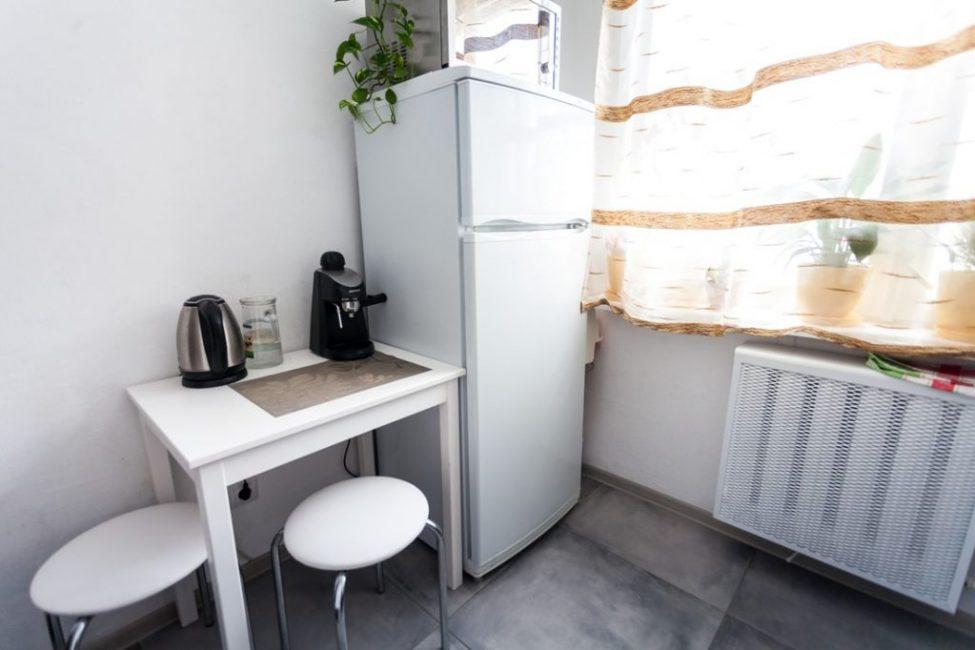 Возле холодильника поместился небольшой обеденный стол и два табурета