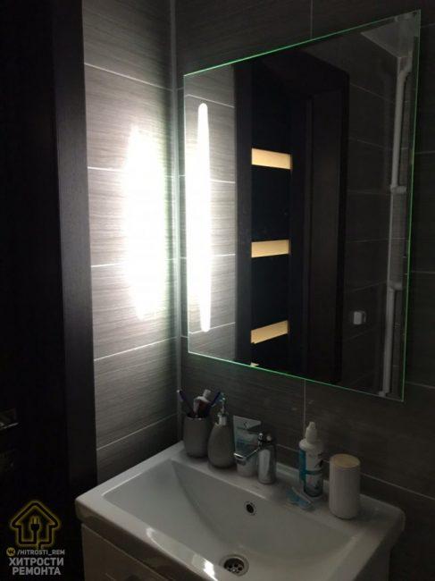 Над раковиной повесили большое зеркало с подсветкой