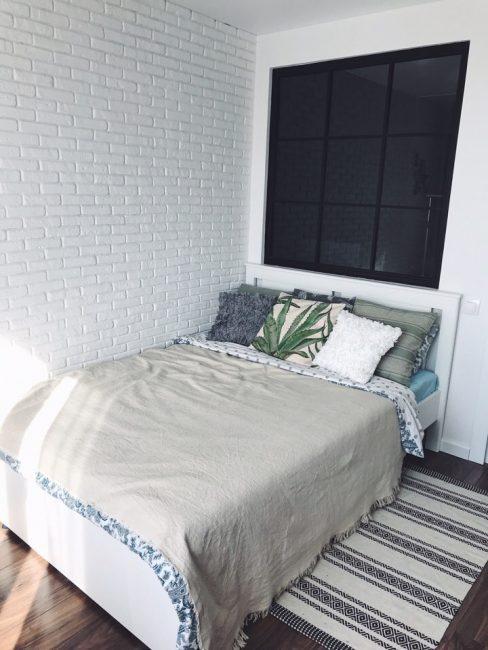 Над кроватью — черное контрастное окно, которое выходит в другую комнату