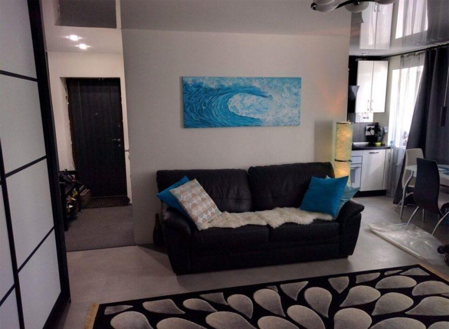 Картина на стене прекрасно сочетается с синими диванными подушками