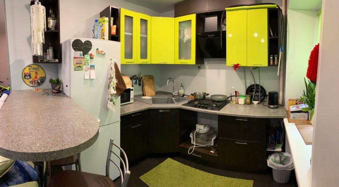 Кухня яркая и акцентная, черная с салатовым. Вместо стола — барная стойка