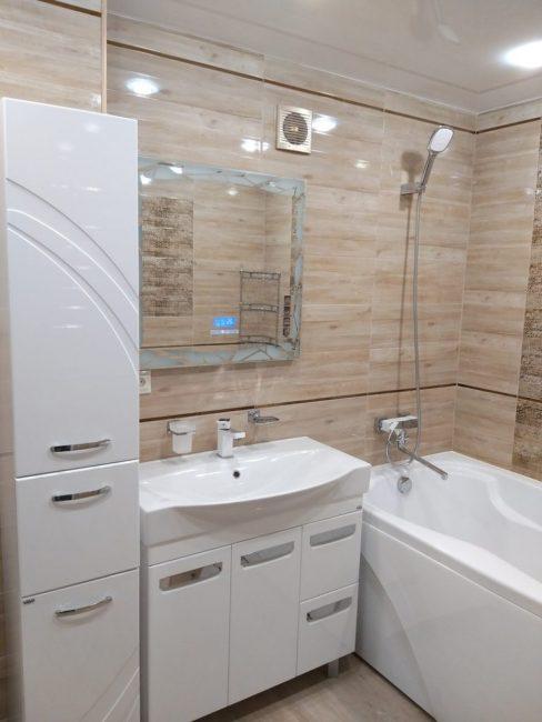 У стены расположился большой умывальник, зеркало над ним и пенал для ванных принадлежностей