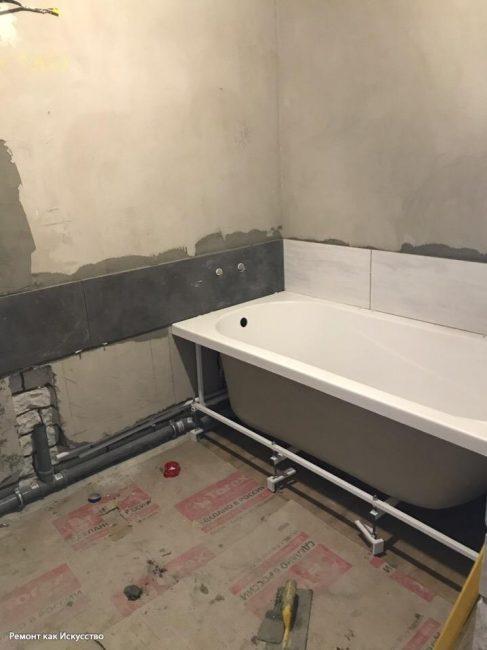 После того, как выровняли стены, зафиксировали акриловую ванну, начали укладывать на стену плитку