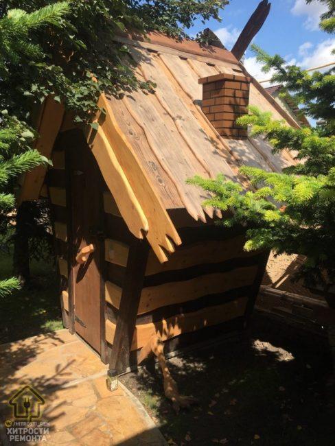 Вот так постройка выглядит снаружи. Она прячется за высокими хвойными деревьями.