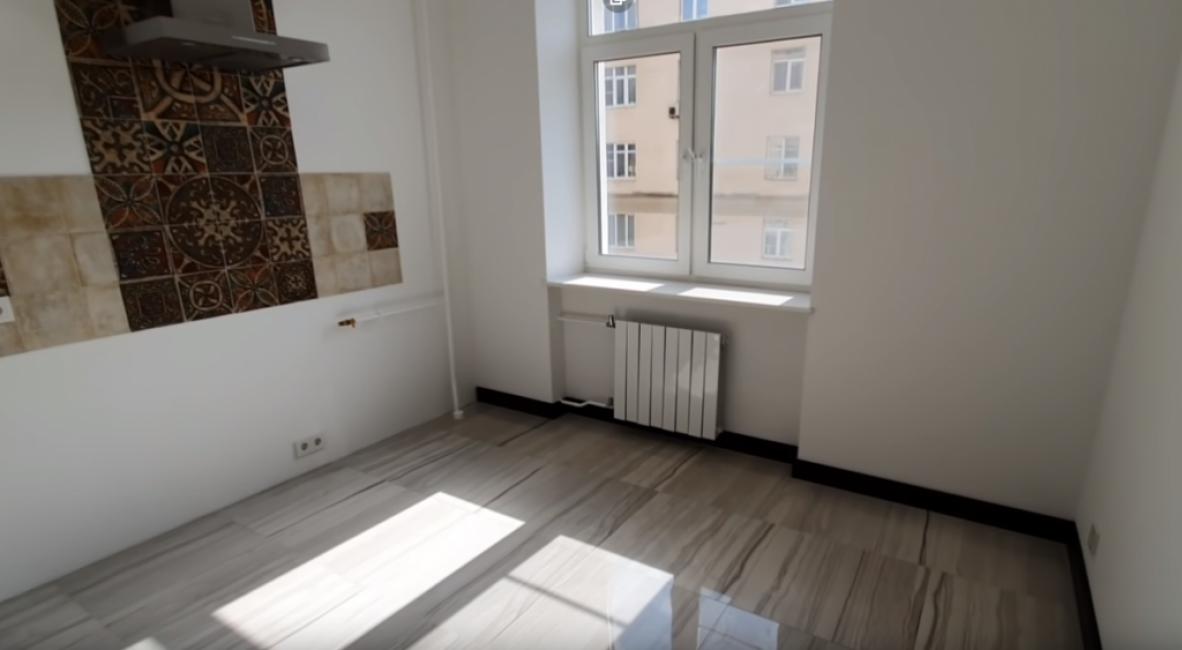 На кухне на полу такая же плитка, как и в коридоре — светлая и глянцевая. Фартук выложили из коричневой и бежевой плитки. Есть датчик протекания воды.