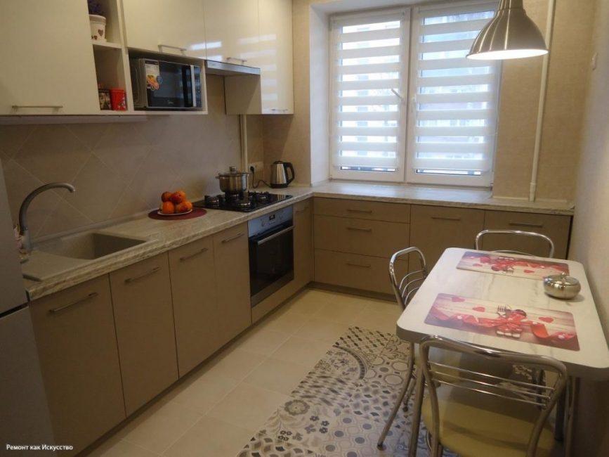 А теперь она выглядит так. Окно поменяли на пластиковое. Заказали кухонный гарнитур бежевого цвета. На пол положили плитку с узором. У стены стоит небольшой кухонный столик с тремя стульями.