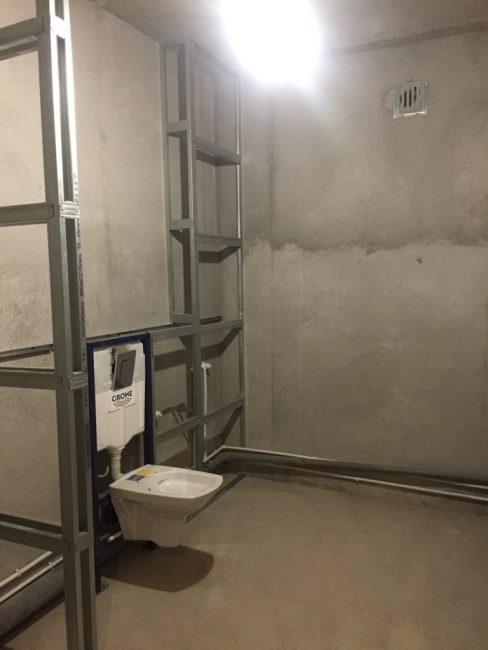 Теперь мужчина начал делать алюминиевый каркас у стены, где поставил унитаз.