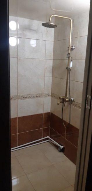 Положили плитку, сделали натяжной потолок молочного цвета и установили кран и душ