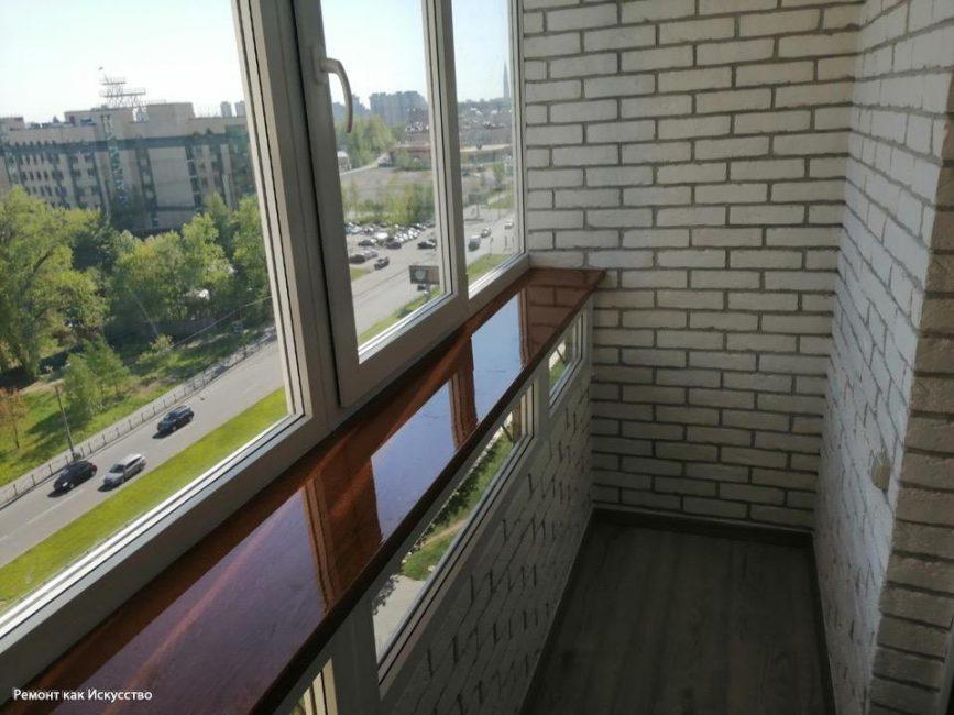 На полу разместился серый ламинат, а на стенах — белый декоративный кирпич