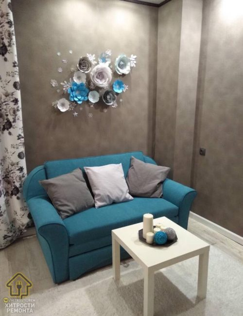 Стену над диваном решили украсить оригинальными цветами. Выглядят они как настоящие и отлично подчеркивают нежность интерьера.