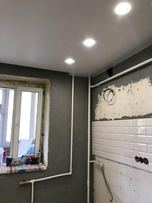 Сделали натяжной потолок с точеными светильниками. Трубы решили не зашивать, а оставить на виду