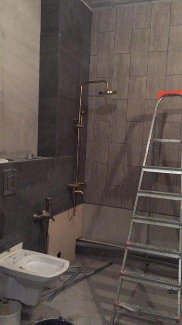 Затем мужчина начал выкладывать стены плиткой и установил краны и душ.