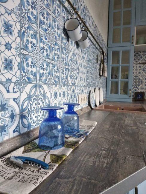 Столешница сделана из керамонранита, имитирующего старое дерево. Эмалированные кружки, стеклянные бокалы синего цвета и даже штопор — все стало предметами интерьера.