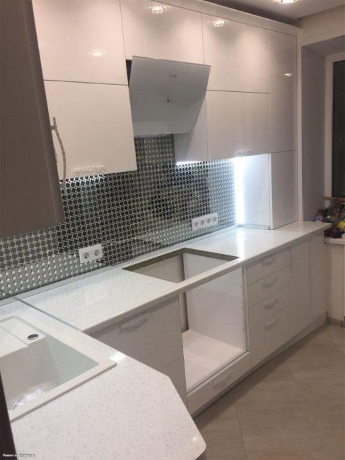 Вся мебель в кухне — белого глянцевого цвета. Оставили место для посудомойки