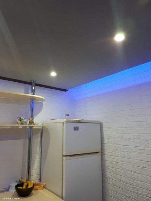 В углу стоит холодильник. В натяжном белом глянцевом потолке установлены точечные светильники + синяя подсветка вокруг