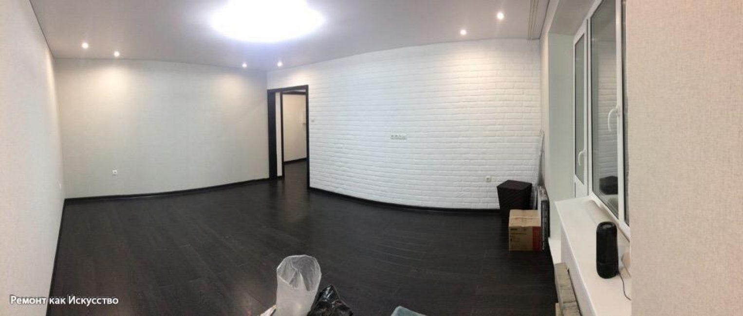 Таким получился зал, с белыми стенами, одной с декоративным кирпичом. Почти черный ламинат, натяжные потолки с центральной люстрой и точечными светильниками