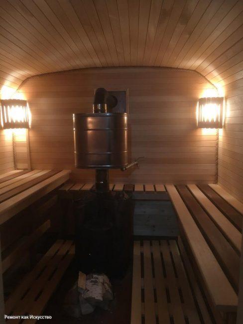 А вот как вагончик выглядит после ремонта. Чисто, красиво. Для сауны мужчина построил деревянные двухуровневые лавки. В каждом углу поставил по светильнику.